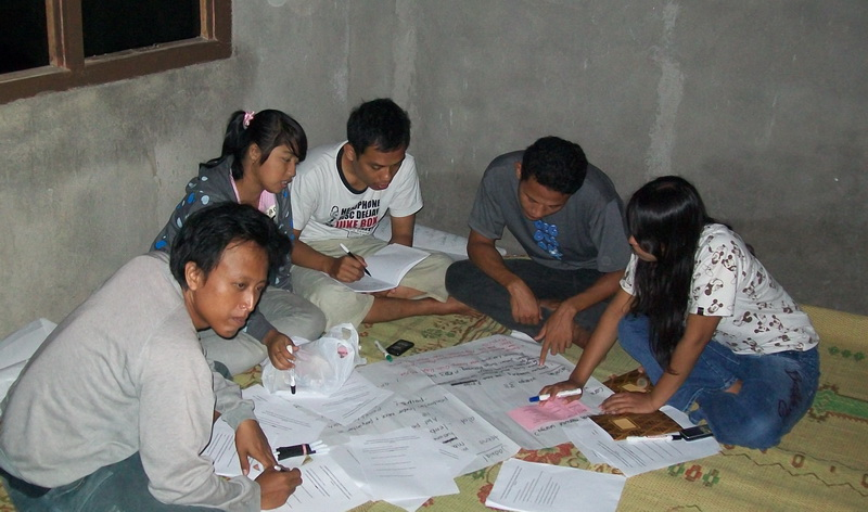 Kelompok remaja menganalisis temuan-temuan penelitian di desanya
